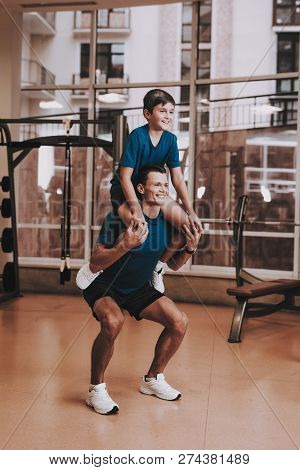 Happy Father And Son Have Fun In Modern Sport Club. Healthy Lifestyle Concept. Sport And Training Co