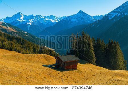 Mountain Landscape. Beautiful Landscape. Austrian Alps. A Small House On The Hillside Against The Ba