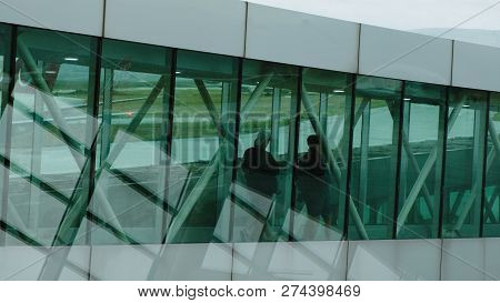 Silhouettes Of Passengers Pass Along The Transparent Corridor