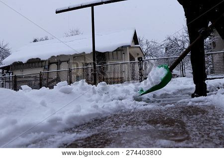 The Winter Is Gaining Strength. A Man With Plastic Shovel Shoveling Snow From Driveways Of Home. Sti