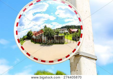 Round Mirror On The Pole For The Safe Movement Of The Car. Reflector On The Road Pole.