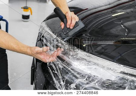 Car Wrapping Specialist Putting Vinyl Foil Or Film On Car. Protective Film On The Car. Applying A Pr