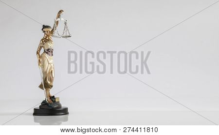 A Figure Of Goddess Of Justice With Scales In Her Hand Is Standing On The Flat Surface At The White