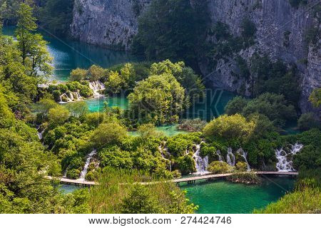 Cascade Limpid Lakes With Waterfalls  And Planked Footway Across The Lake In Plitvice Lakes National
