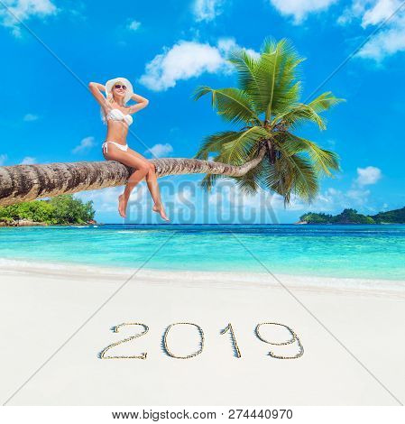 Cute Blonde Woman In White Bikini And Hat At Palm Tree Against Tropical Ocean Beach With Inscription