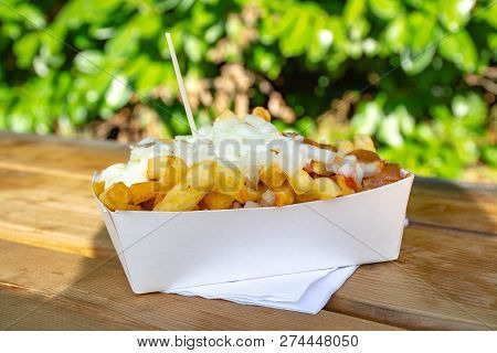 Portion Of Fresh Fried Belgium Potatoes Sticks With Inion, Ketshup And Sate Sauce Served Outside