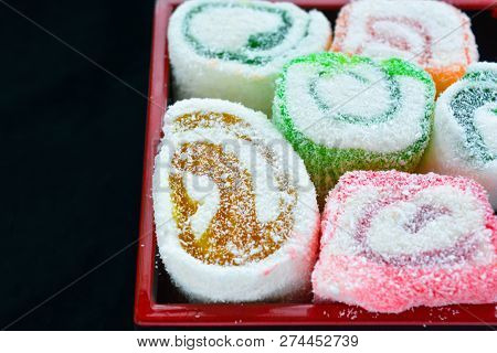 Delicious colorful rolls of Lokum with fruit marmalade jam in japanese style in japanese lacquer black and red wooden box. Tasty dessert of national turkish sweet poster