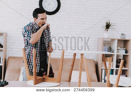 Young Man Assembling Coffee Table And Stools. Furniture Fittings. Engineer With Tool. Young Man At H