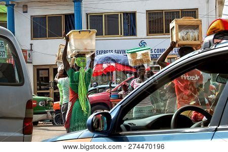 Accra, Ghana, West Africa -july 23, 2013: African Women Carry Bowls On Their Heads And Sell Food For