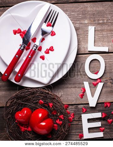St. Valentine Day Table Setting. White Plates In Form Of Heart, Cutlery, Decorative Hearts In Nest A