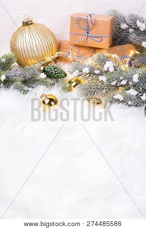 Golden Balls, Wrapped Presents, Fir Tree Branches And Fairy Lights On White Textured Background. Sel
