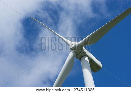 Ecology Concept: Blue Sky, White Clouds And Wind Turbine. Wind Generator For Electricity, Alternativ
