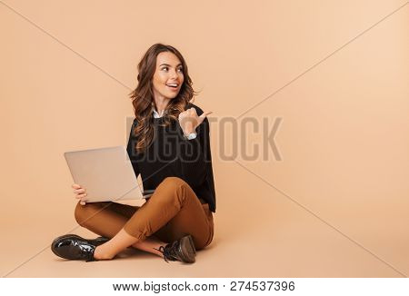Image of caucasian woman 20s using laptop while sitting on floor isolated over beige background poster