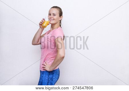 1 White Girl In Sports Clothes Drinking Orange Juice, Girl Standing Sideways In A Pink Sports Top