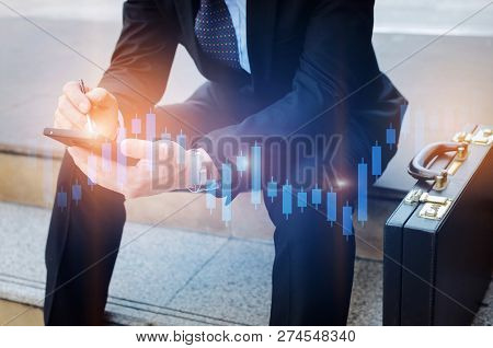 Young Investor Or Business Man And Using Mobile Phone With Graphic Candle Stick Graph Chart Of Stock