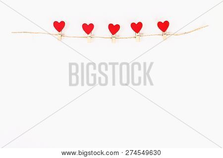 Valentine Day Layout. Red Hearts On Wooden Clothespins On A Jute Twine On A White Background. St. Va