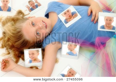 Beautiful young girl child in dance tutu laying on floor after playing with instant camera.