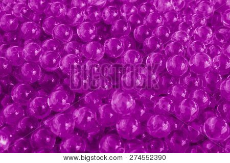 Water purple gel balls with bokeh. Polymer gel. Silica gel. Balls of purple hydrogel. Crystal liquid ball with reflection. Purple balls texture background. Macro poster