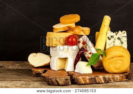 Various Kinds Of Cheese Served On Wooden Table. Wooden Board With Different Kinds Of Delicious Chees