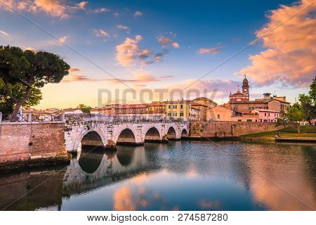 Rimini Cityscape. Tiberius Bridge Famous Sightseeing In Rimini At Dawn. Summer Sunrise In Rimini His