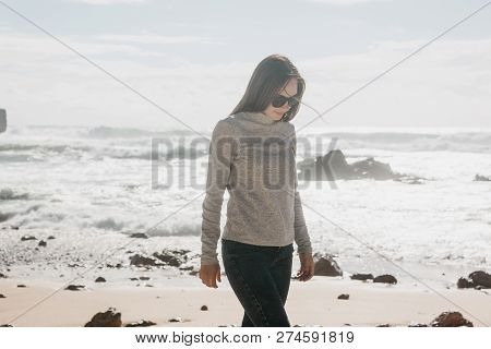 A Young Beautiful Girl Walks Along The Coast In Solitude And Thinks Or Is Engaged In Looking For The