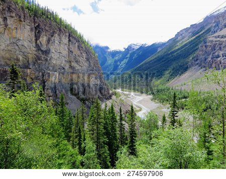 An Epic Nature Picture Deep In The Forests Of The Canadian Rockies With High Rocky Cliffs And A Rive