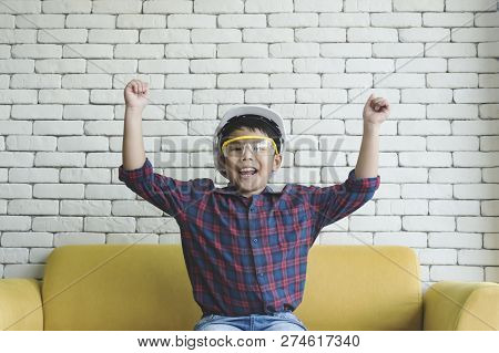 Little Boy Wearing A Engineering Helmet And Smilling At Home.
