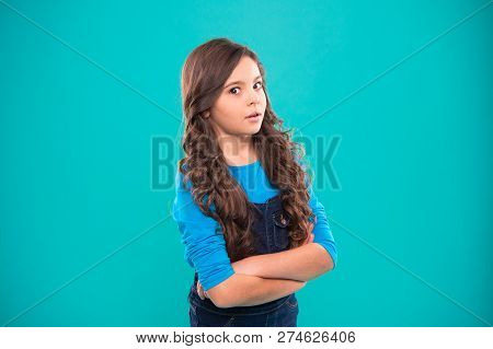 Girl Curly Hairstyle Feels Confident. Child Hold Hands Confidently Crossed Chest. Child Psychology A