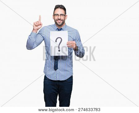Handsome young business man holding paper with question mark over isolated background surprised with an idea or question pointing finger with happy face, number one