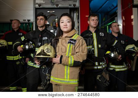 Photo of four young male and female firefighters on background of fire truck