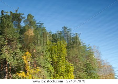 Abstract Background: Reflection Of The Autumn Deciduous Forest In The Pond. Blue Sky And Trees Refle