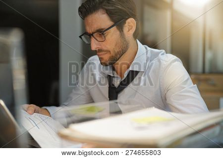 Handsome businessman working late at night in modern office