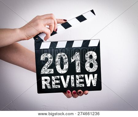 2018 Review Concept. Female Hands Holding Movie Clapper