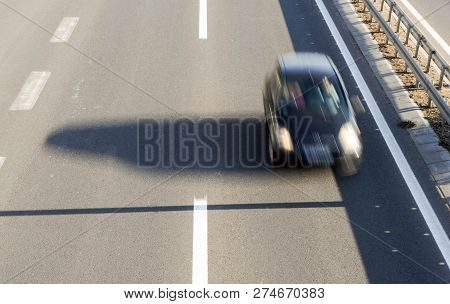 Aerial View Of A Car Driving Fast On The Highway With Three Lanes And Road Fence Barrier