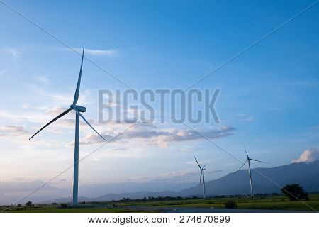 Wind Turbines Farm And Agricultural Fields On Blue Sky. Turbine Green Energy Electricity Or Wind Tur