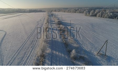 Aerial View Winter Landscape Countryside Road Through Winter Field With Forest. Winter Forest On Sun