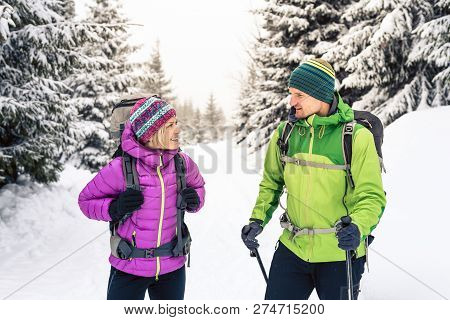 Man And Woman Happy Couple Hikers Trekking In White Winter Woods And Mountains. Young Hiking Team, P