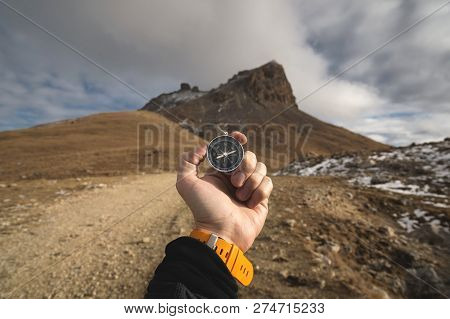 A Male Hiker Is Looking For A Direction With A Magnetic Compass In The Mountains In The Fall. Point