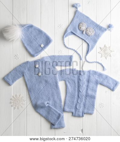 Blue small knitted clothes for babies composed on the white table