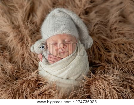 Cute little baby in hat with toy sweetly sleeping covered in blanket