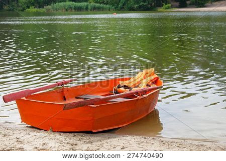 Outfit Of Lifeguard On Water In Summer Boat, Life Jacket, Lifebuoy In Orange Color. Help In Water.