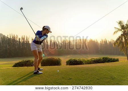 Asian Woman Golf Player Doing Golf Swing Tee Off On The Green Sunset Evening Time, She Presumably Do