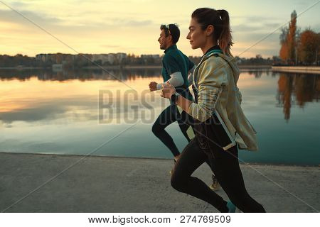 Motivated Couple Of Runners Out For A Run On The Lake At The Sunrise. Young Man And Woman In Sport C