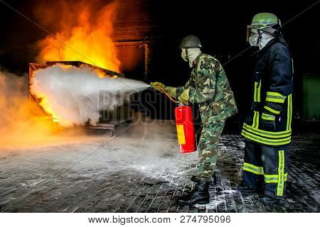 Firefighters Training For Fire Fighting In Germany. Firefighter In Fire Protection Suit Spraying Wat
