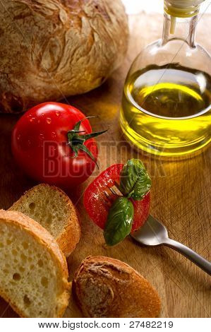 fork with slice tomato bread and olive oil
