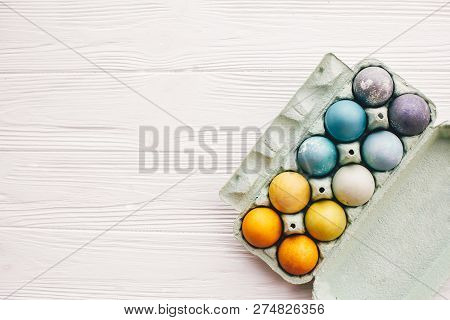 Stylish Easter Eggs In Carton Tray On White Wooden Background, Top View. Modern Colorful Easter Eggs