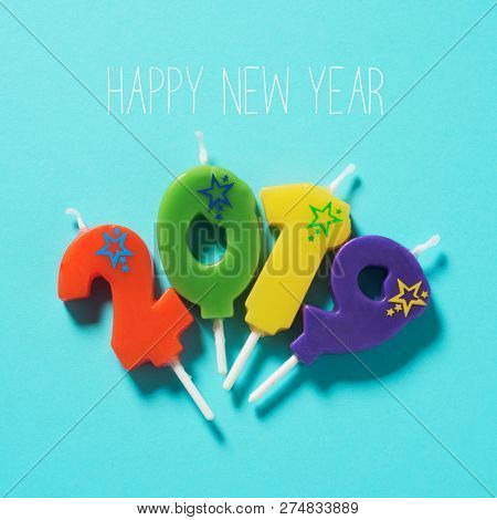 high angle view of some number-shaped candles of different colors forming the number 2019, and the text happy new year on a bright blue background