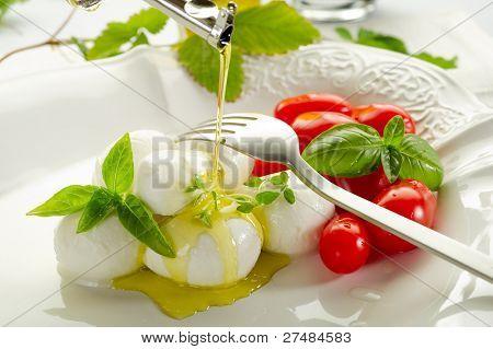 olive oil over mozzarella and tomatoes
