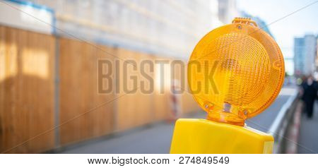 Road construction concept. Orange reflector warning light protects the drivers. Blur background, space, banner.