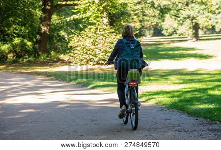 Healthy lifestyle. Woman is riding a bicycle in a path of Tiergarten park, Berlin, Germany. Nature background.